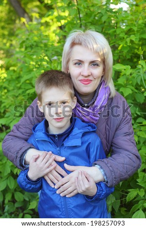 pretty young woman embracing her little son in the park