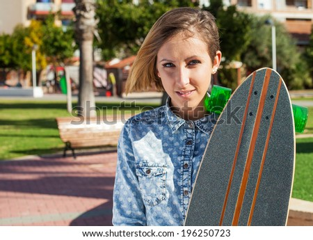 pretty young woman holding a skate in a park