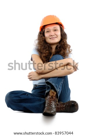 Pretty young woman in a hard hat sitting isolated on white background. Construction worker or intern concept.