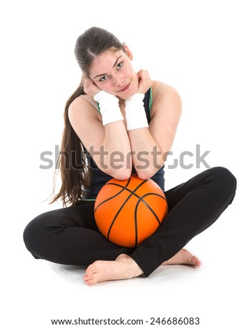 Pretty young woman in sports wear sitting on floor with a basketball, isolated over white