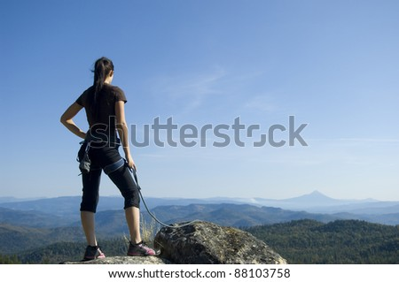 Pretty Young Woman looking off a cliff into valley