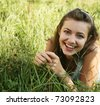 pretty young woman outdoor in the grass in summertime - stock