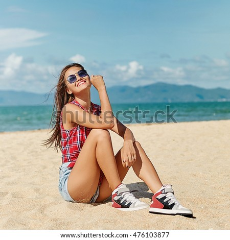 Pretty young woman posing on the beach
