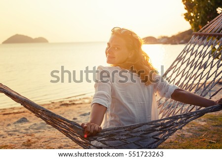 pretty young woman sitting on a hammock at sunset overlooking the sea. Vacation, travel, holiday at the sea concept