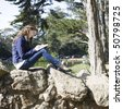 Pretty Young Woman Sitting on Rocks in a Park Writing in a Journal - stock photo
