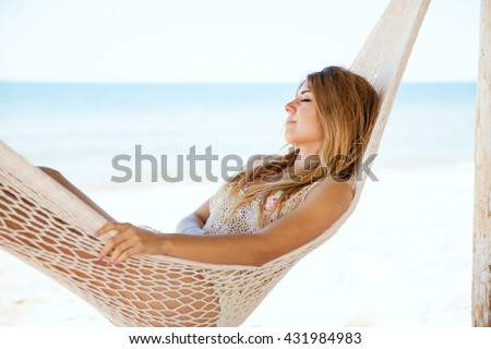 Pretty young woman taking a nap in a hammock during her vacation at the beach