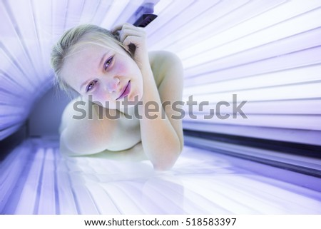 Pretty, young woman tanning her skin in a modern solarium (shallow DOF; color toned image)