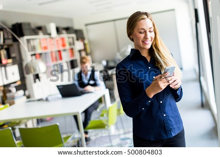 Pretty young woman using mobile phone in the office