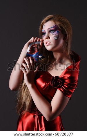pretty young woman with party make up isolated on grey background