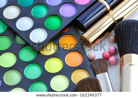 Professional eye shadows palette with makeup brushes and lipsticks
