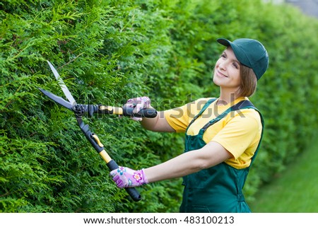 professional gardener at work. smiling young woman gardener working with hedge shears in the yard. garden worker trimming plants. topiary art. gardening service and business concept