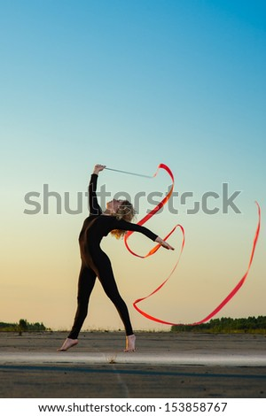 Professional gymnast woman dancer posing with ribbon