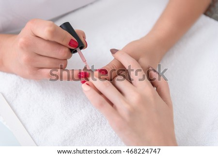 Professional manicurist paining female fingernails