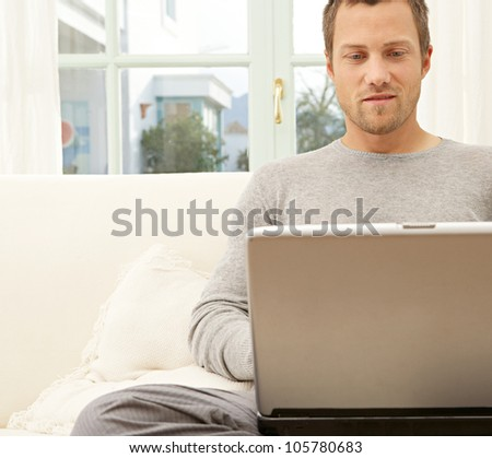 Professional young man using a laptop and a smart phone while sitting on a white sofa at home.