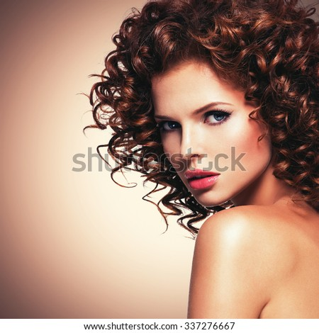 Profile portrait of beautiful young sexy woman with brunette curly hair looking at camera.