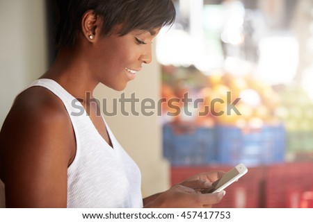 Profile portrait of young good-looking dark skinned smiling woman leaning against the white wall, holding smartphone, using free Internet, checking e-mail, watching funny videos, updating applications