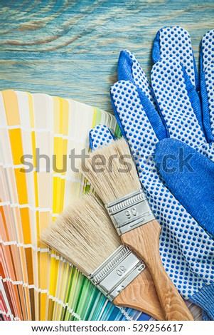 Protective gloves color palette paintbrushes on wooden board construction concept.