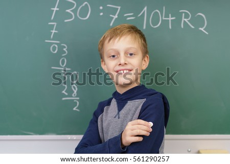 Proud young boy doing mathematics in school posing in front of an answered question on the blackboard with a happy grin of success
