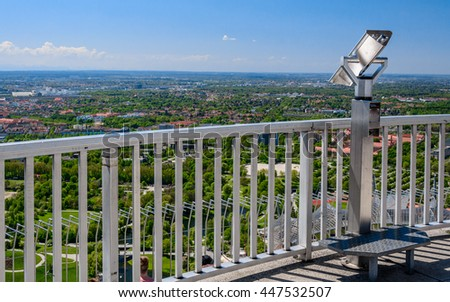 Public metal telescope (binoscope, binocular) with footrest on the top of observation deck - view to the park and city landscape - panorama from height of bird's flight