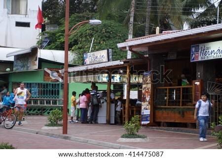 PUERTO AYORA, ECUADOR - CIRCA MAY 2013: Locals gather in the park in the evening, in front of restaurants and shops