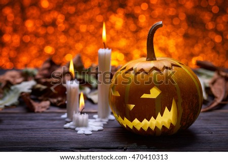 Pumpkin for Halloween, lamp pumpkin, antique wood, celebrating halloween, smiley on a pumpkin, paraffin candles, bright background, angry face, burning candles, autumn dry leaves