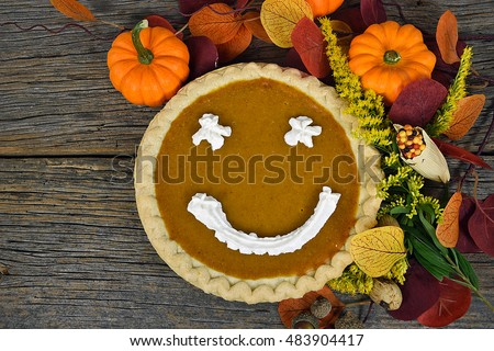 pumpkin pie with happy face in fall leaves and gourds on rustic barn wood