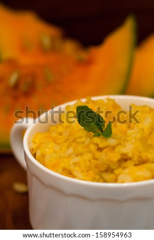 Pumpkin porridge and pumpkins on wooden table