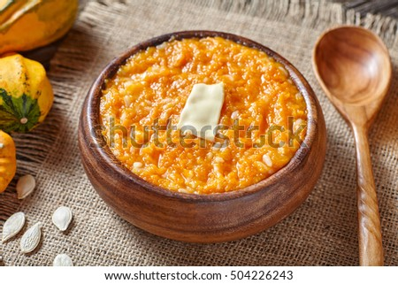 Pumpkin rice porridge pudding breakfast homemade sweet baked dessert healthy organic nutrition diet food with butter traditional autumn meal on vintage table background