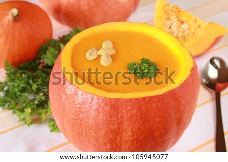 Pumpkin soup in a pumpkin and more pumpkins in the background