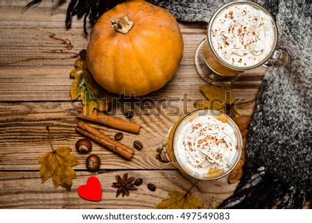 Pumpkin  spice latte with whipped cream on the rustic wooden background.