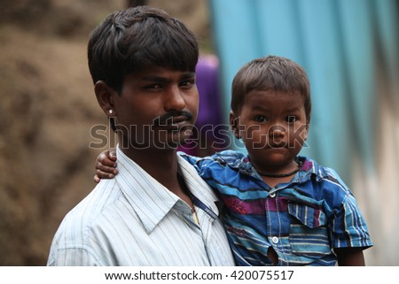 Pune, India - July 16, 2015: A little boy with his poor father who is a construction worker, in India