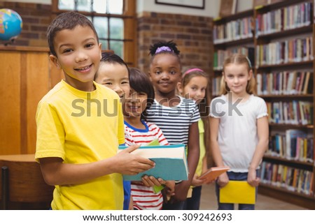 Pupils holding books from shelf in library at the elementary school