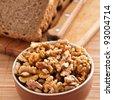 purified kernels walnuts in bowl,cutting board cut rye bread, knife background wooden table - stock photo