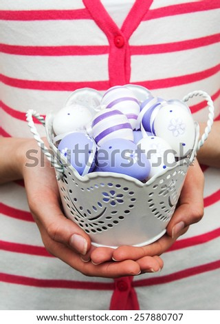 Purple easter eggs in metal pot by hands