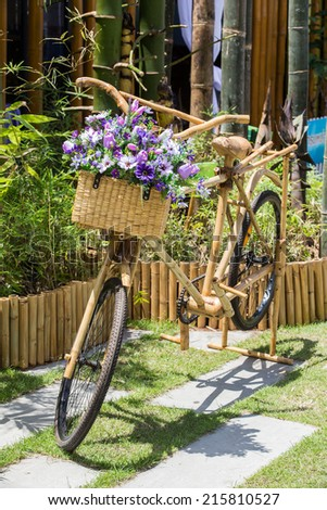 Purple flowers on a bamboo bicycle basket.