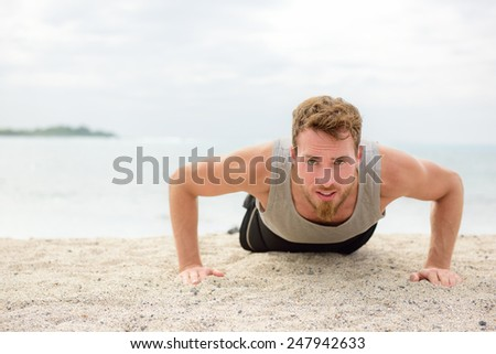 Push-up crossfit man fitness model training pushups on beach outdoors. Fit male fitness trainer working out exercising in summer on beach.