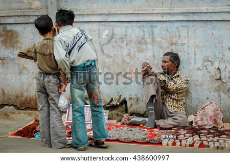 PUSHKAR, INDIA - NOVEMBER 14, 2009: Two young boys take interest in an item for sale at the open market