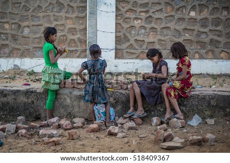 PUSHKAR, RAJASTHAN, INDIA - DECEMBER 4, 2016: Indian girls playing with dolls on the street.