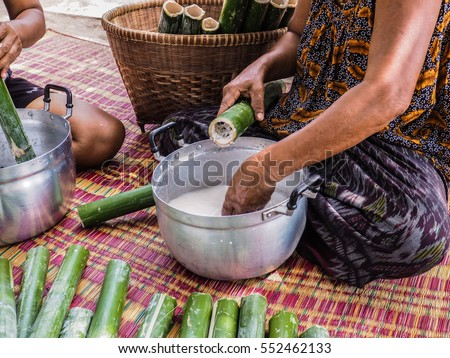 Put the rice with mixed ingredients into Bamboos tube. This is a part of cooking process of glutinous rice roasted in bamboo joints. Picture from Thailand country.