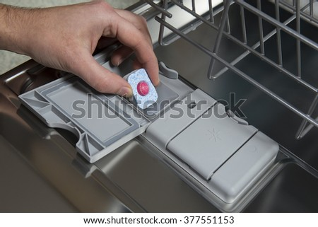 Putting tablet in dishwasher machine