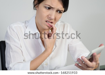 Puzzled woman thinking hard and grimacing as she tries to find an answer to a problem holding a calculator in her hand