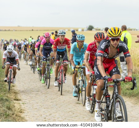 QUIEVY, FRANCE- JUL 07: The peloton riding on a cobblestone road during the stage 4 of Le Tour de France in Quievy, France, on 07 July 2015