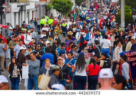 QUITO, ECUADOR - JULY 7, 2015: Crowded avenue with lots of people walking, police watching and guarding people