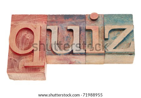 quiz word in vintage wood letterpress printing blocks, stained by color inks, isolated on white