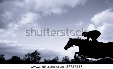 race horse jumping over a hurdle at speed photographed in silhouette with room for titles