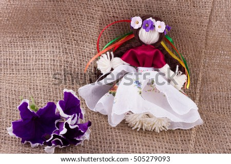Rag doll in tunic and wreath with ribbons on a background of burlap, handmade, purple Petunia flowers