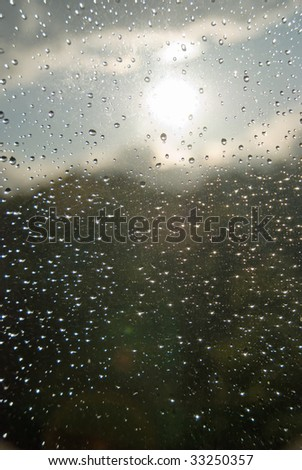 Rain drops on a window glass, with un-sharpen clouds and forest in the background.
