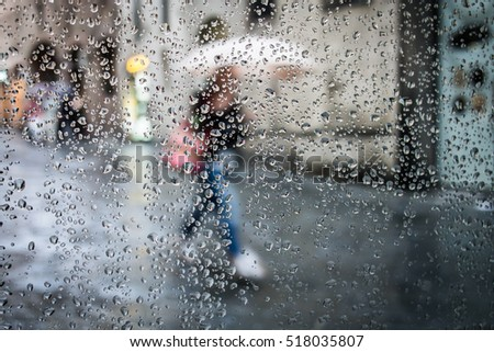 Rain in street and silhouette with umbrella