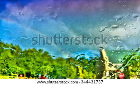 Raindrops create abstract view with rainbow in distance