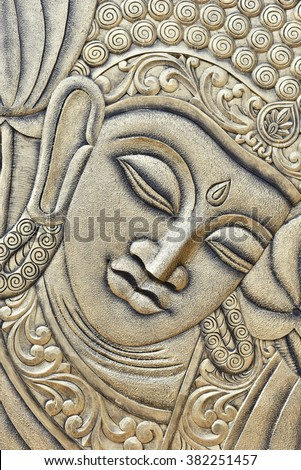 Raised crafted Buddha close up on wood, whole background